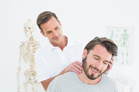 Male chiropractor doing neck adjustment in the medical office